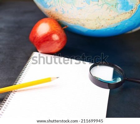 Studying geography composition of an opened note book, magnifying glass, pencil and red apple next to a globe over the blackboard's surface - stock photo