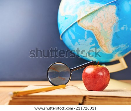 Studying geography composition of the red apple, old books, globe and magnifying glass against the blackboard background - stock photo