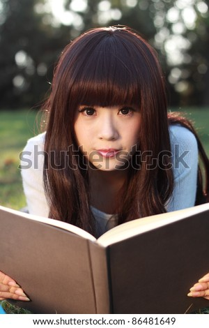 Studying happy young woman reading her book. - stock photo