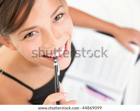 Studying happy young woman reading her book for school. Beautiful mixed race asian caucasian girl. - stock photo