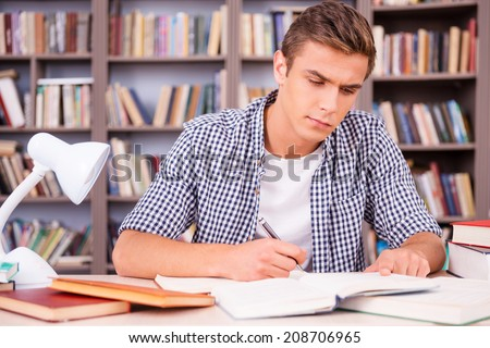 Studying hard for good grades. Confident young man making research while sitting in library - stock photo