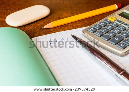 Studying in the school, solving mathematical problems, a pencil and eraser with a calculator on the table - stock photo