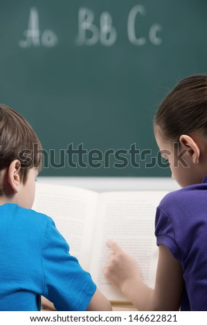Studying together. Rear view of two little classmates reading a book together - stock photo