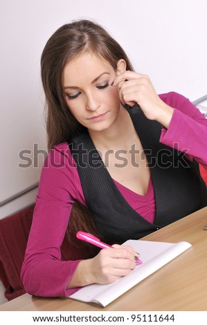 studying woman is sitting at the table - stock photo
