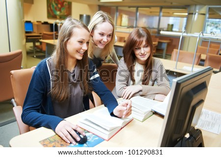 Studying young teenage college student girls in a library with computer - stock photo