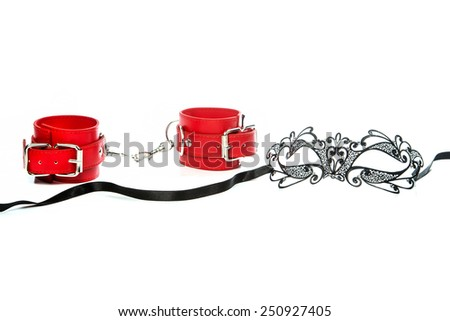 Stuff for sexual role playing: fetish mask in venetian style together with a pair of red leather hand cuffs. - stock photo