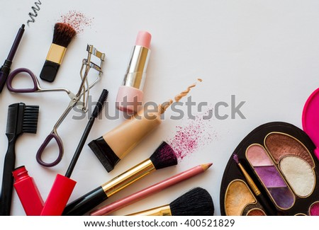 stuff from the female cosmetic bags. cosmetics and makeup brushes on a white background - stock photo