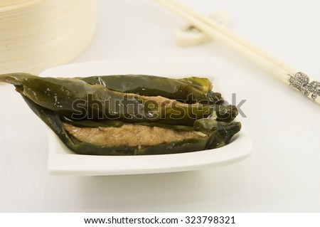 Stuff green chilis with minced meat mix with fish paste. A dim sum style Chinese cuisine prepared as small bite-size portion of food traditionally served in small steamer basket or on small plate. - stock photo