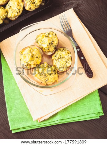 Stuffed baked potato with eggs, cheese and spices - stock photo