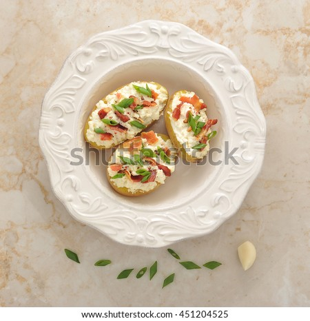 stuffed baked potatoes in jacket with bacon and cheese on marble background. the view from the top - stock photo