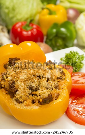 """stuffed bell pepper with beef and rice topped with parmesan cheese and garnished with sliced tomatoes and parsley""""stuffed bell pepper"""" - stock photo"""