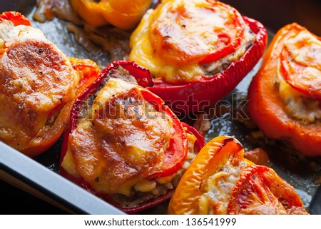 Stuffed bell peppers on black baking pan - stock photo