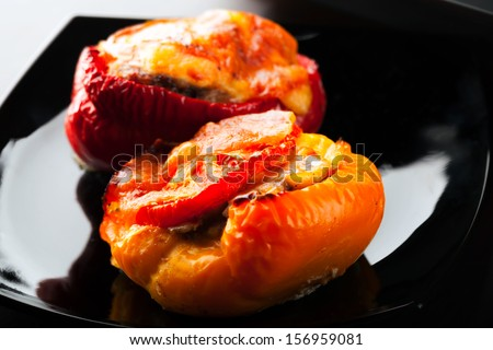 Stuffed bell peppers with chopped meat, cheese and tomato lay on black plate - stock photo