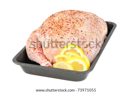 Stuffed chicken  on a baking sheet, decorated with lemon.  Isolated  on white. - stock photo