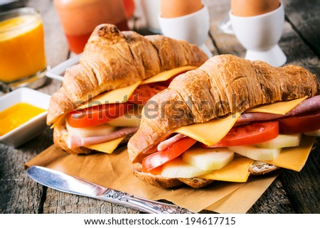 Stuffed croissants sandwich on the table.Selective focus on the front croissant  - stock photo