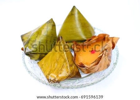 Stuffed Dough Pyramids and basket-shaped Chinese puddings sets on transparent glass dish on white background.