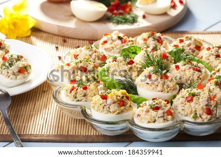 stuffed eggs with ham, red pepper and dill on plate