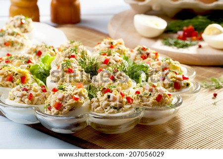 stuffed eggs with ham, red pepper and dill on plate - stock photo