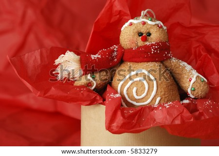 Stuffed gingerbread man ornament (made of fabric to look like a cookie) displayed popping up out of box filled with red tissue paper and sprinkled with snow glitter.  Macro image with shallow dof - stock photo