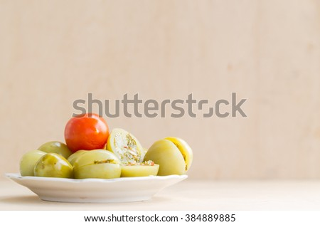 Stuffed green tomatoes with red tomato on white plate. Plate with tomatoes are located on wooden background. - stock photo