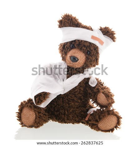 Stuffed hand made bear with pain and plaster isolated over white background - stock photo