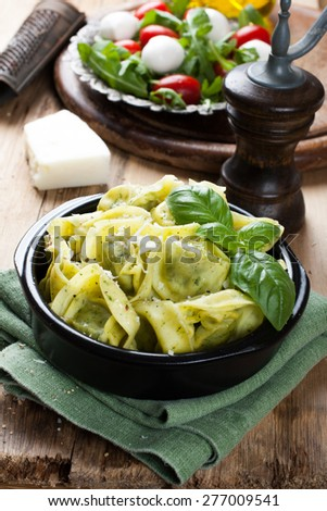 Stuffed Italian tortellini pasta noodles filled with ricotta and spinach and fresh basil served with pecorino and fresh salad - rucola, cherry tomatoes and mozzarella. Selective focus. - stock photo