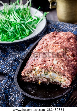 Stuffed meat roll on iron pan. Style rustic. Selective focus. - stock photo