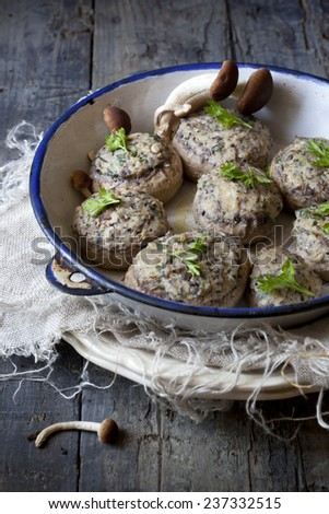 stuffed mushrooms on vintage enamelled tin on rustic wooden table with frayed cloth - stock photo