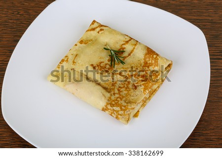 Stuffed pancake with meat on the wood background
