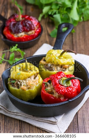 Stuffed peppers in a cast iron skillet on a wooden background - stock photo