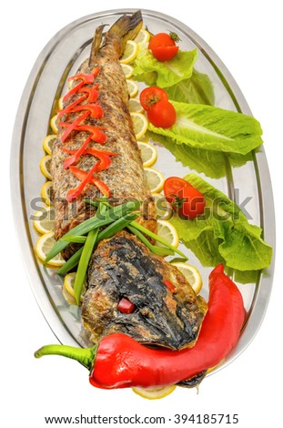 Stuffed pike, decorated with lemon slices, pepper, tomato, green onion and lettuce, on white background. - stock photo
