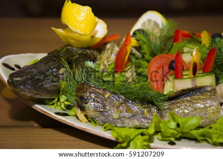 Stuffed pike with vegetables and herbs. Hearty dish in one of the bars.