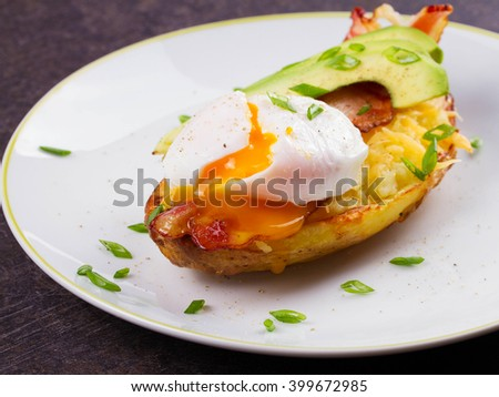 Stuffed potato with bacon, poached egg, kiwi, cheese and spring onion. - stock photo