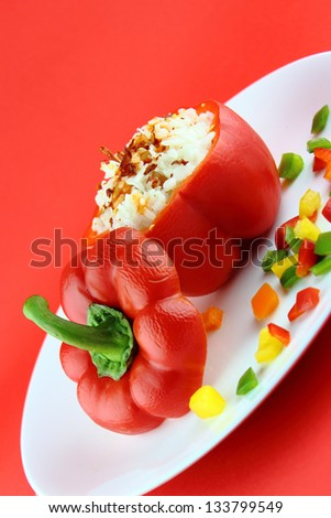 Stuffed red pepper in a dish on red background .