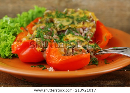 Stuffed red pepper with lettuce on plate on wooden table
