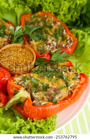 Stuffed red peppers on plate on napkin close up - stock photo