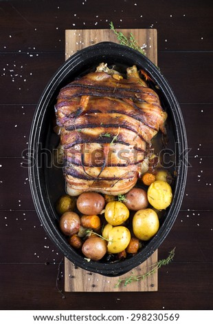 Stuffed roasted chicken wrapped in bacon with potatoes, carrots and mushrooms - stock photo