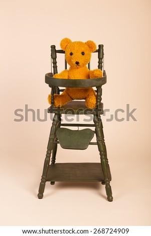 Stuffed self made bear sitting in child seat - stock photo