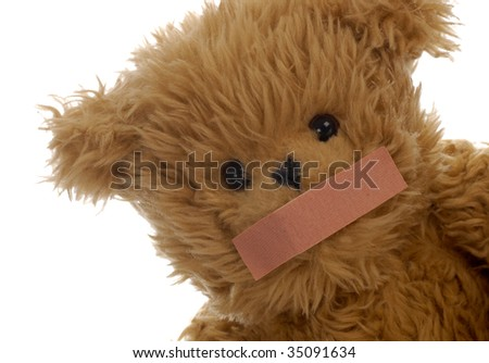 stuffed teddy bear with bandaid on mouth - stock photo