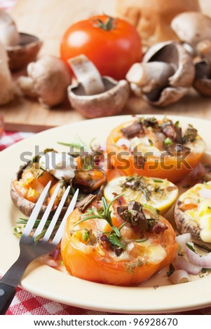 Stuffed tomato with mushrooms, cheese and herbs - stock photo
