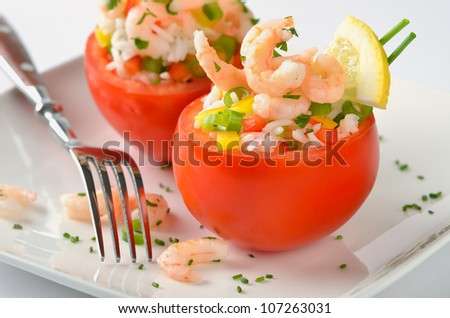 Stuffed tomatoes with shrimps, rice, bell peppers, spring onions, lemon, chives and parsley. A very delicious appetizer - stock photo