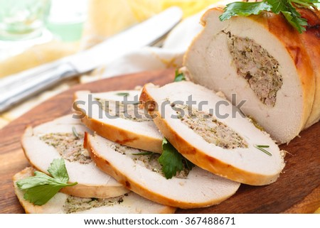 Stuffed turkey breast with parsley and rosemary on cutting board. - stock photo
