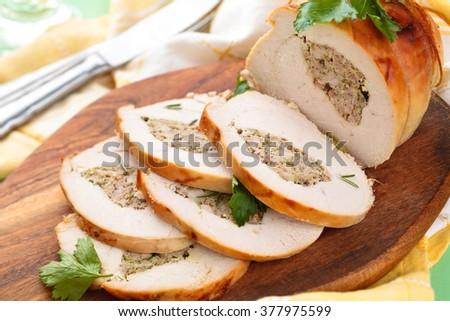 Stuffed turkey breast with parsley  on cutting board. - stock photo