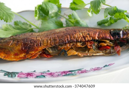 Stuffed with vegetables grilled fish (saury). Grilled fish is very good with vegetables and cilantro. Grilled fish is very popular and famous delicacy in many cuisines. - stock photo