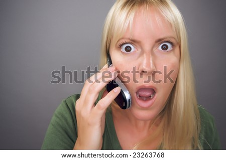 Stunned Blond Woman Using Cell Phone Against a Grey Background. - stock photo