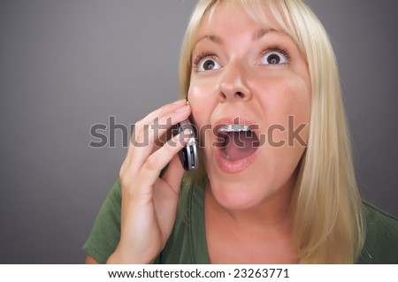 Stunned Blond Woman Using Cell Phone Against a Grey Background.