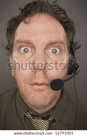 Stunned Businessman Wearing Phone Headset Against a Grey Background. - stock photo