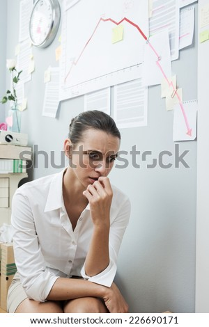 Stunned businesswoman checking a financial business chart on office wall with arrow going down.