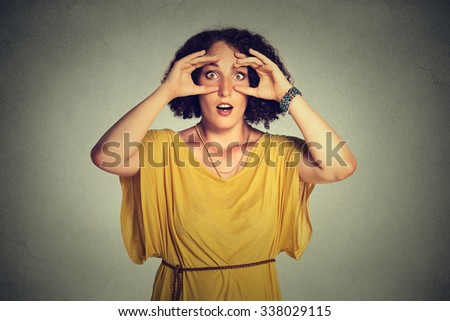 stunned curious woman, peeking looking through fingers like binoculars searching - stock photo