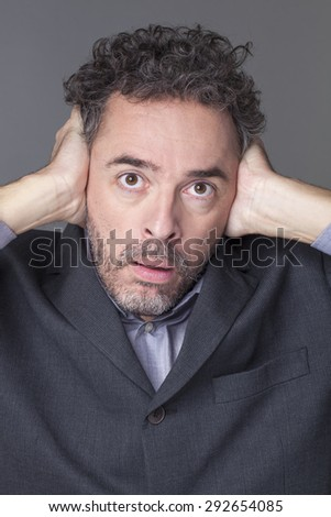 stunned 40's businessman with curly grey hair covering closed ears to avoid listening management noise - stock photo